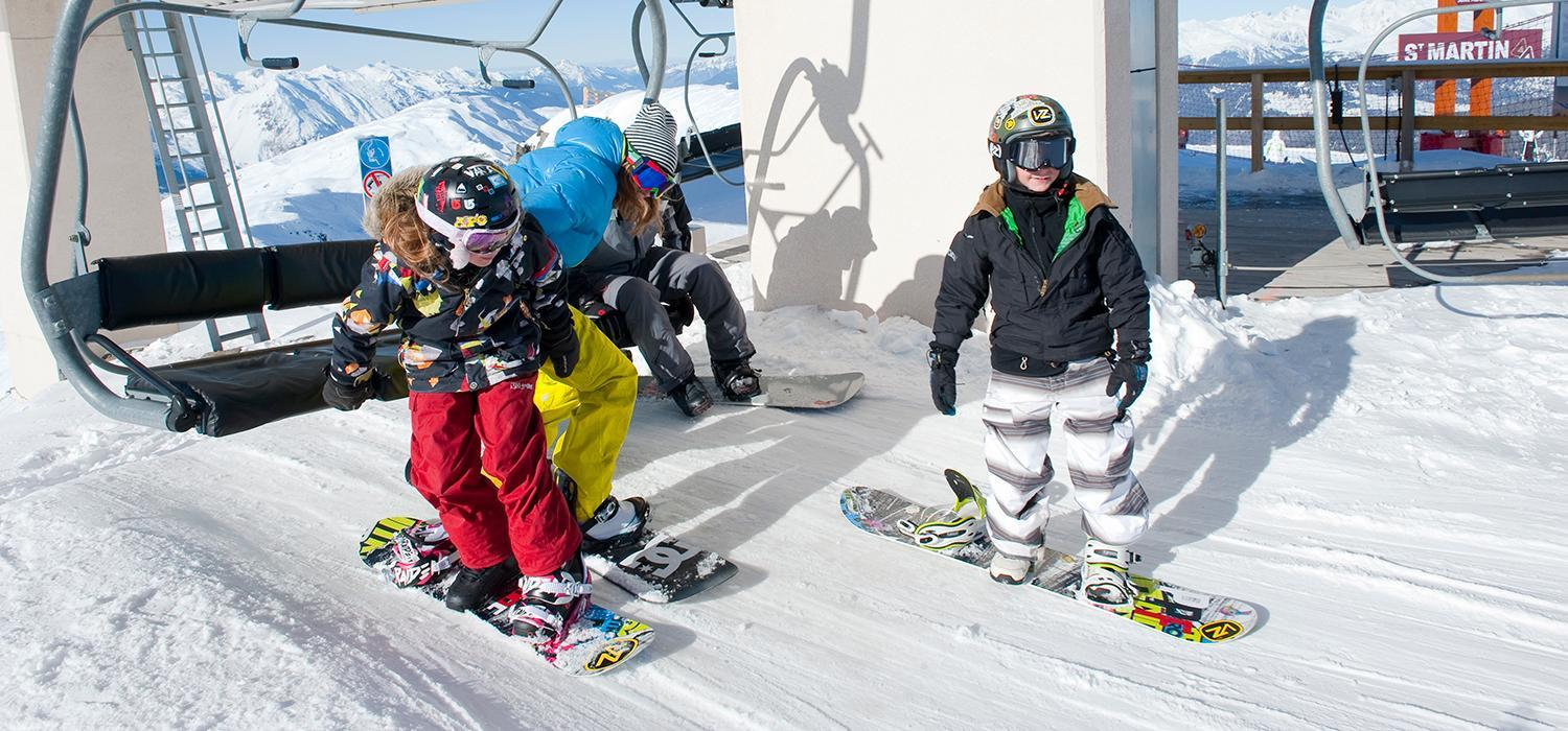 snowboarders getting off a lift