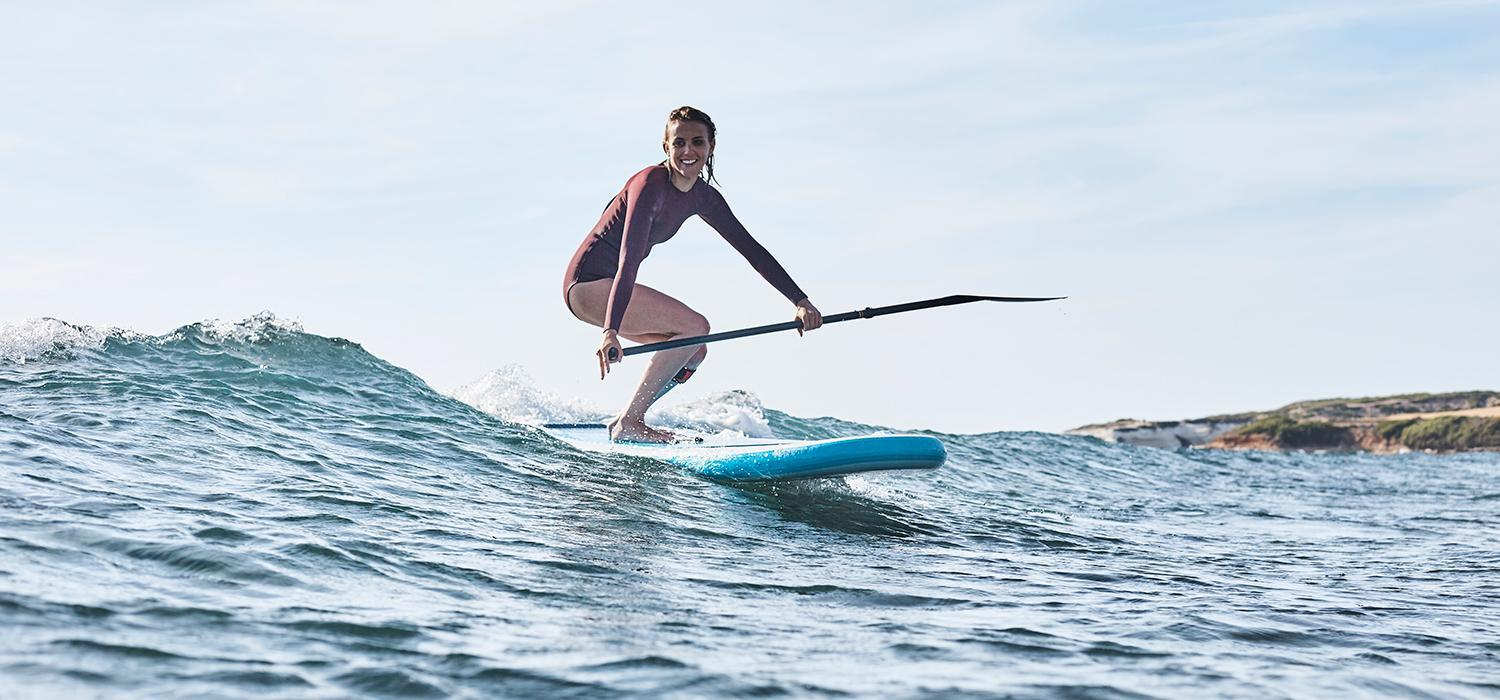 Stand up paddle boarding on a wave