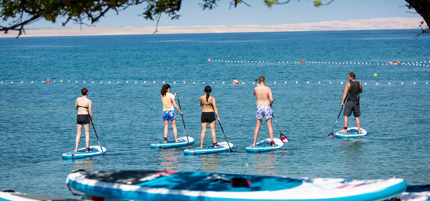 Group of people stand up paddle boarding