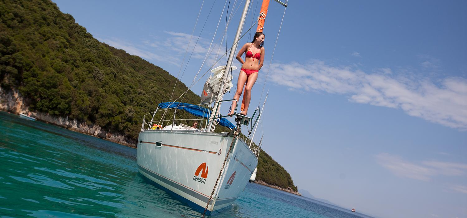 young woman standing on bow of yacht in Greece