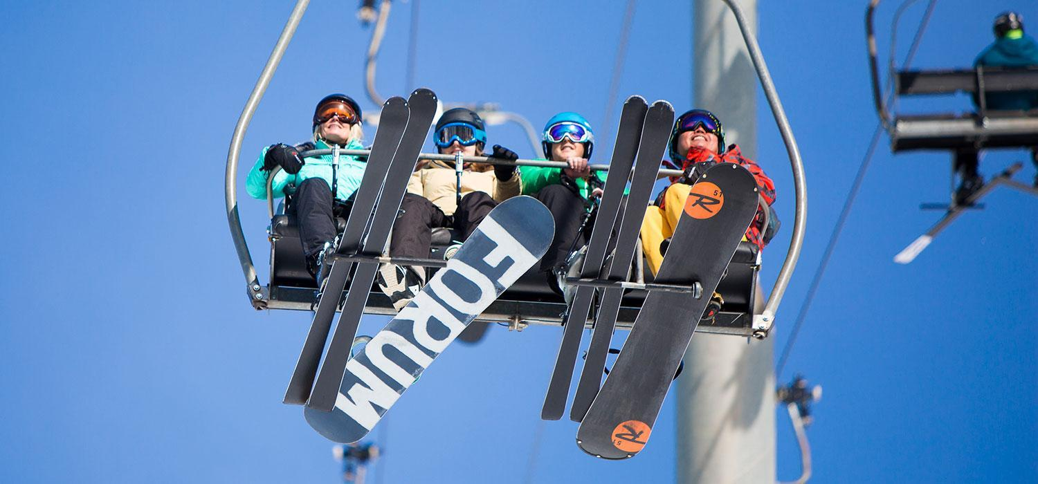 skiers and snowboarders on a chairlift