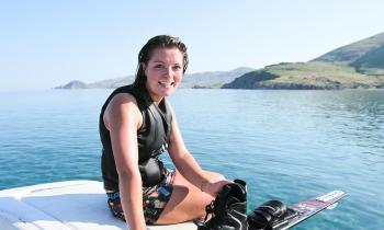 Girl on back of boat after water skiing