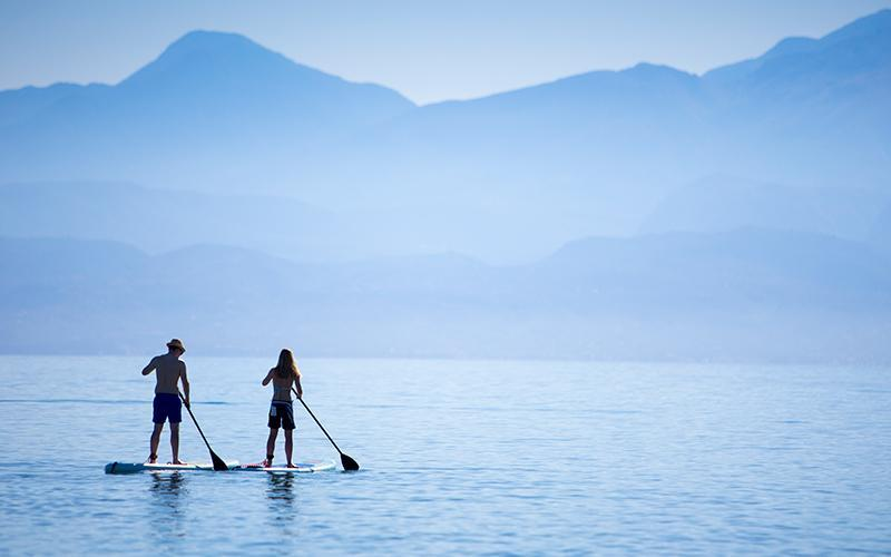 couple stand up paddle boarding in Greece