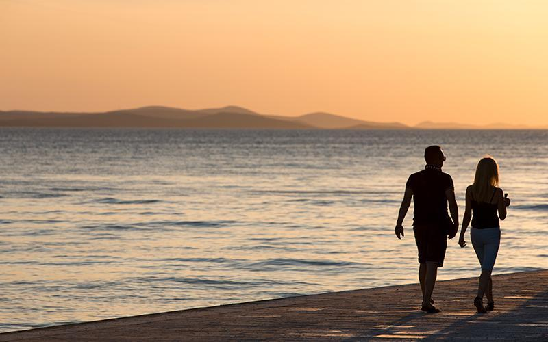 Couple walking on seafront at sunset
